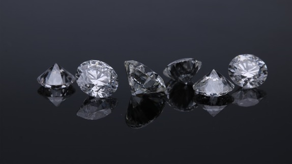 A row of loose diamonds photographed from closeup.